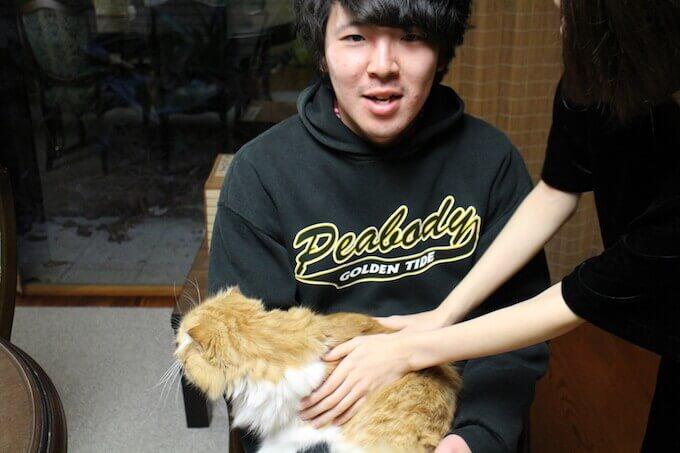 猫を持つ男性